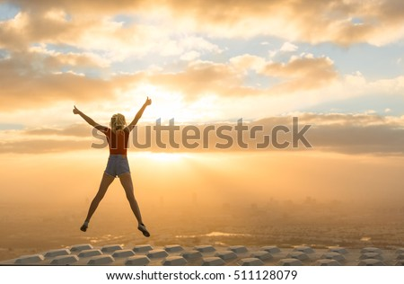 Success concept. Celebrating woman on top of skyscraper overlooking the city at sunrise.