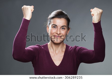 success concept - happy young woman with both hands up holding her fists up for winning competition with serenity,using body language