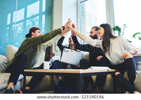Success concept, Young talented crew of graphic designers made good job feeling proud and exciting when finishing project in friendly atmosphere while high-fiving with colleagues in coworking space