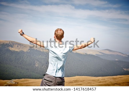 Success Freedom Concept. Young man in the mountains Success Freedom Concept.