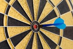 Success hitting target aim goal achievement. Blue Dart in bull's eye. Retro darts aim. (soft focus, toned photo)