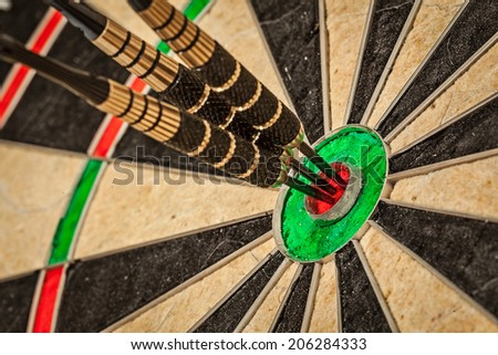Success hitting target aim goal achievement concept background - three darts in bull\'s eye close up