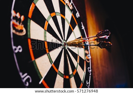 Success hitting target aim goal achievement concept background - three darts in bull's eye close up. red three darts arrows in the target center business goal concept