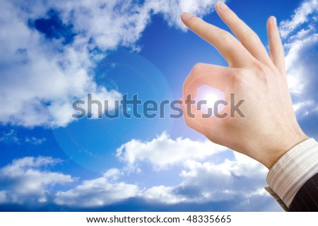 Success in business conceptual image. Businessman hand against the blue sky.