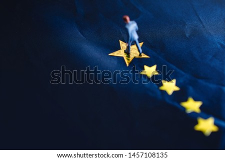 Success in Business or Talent Concept. Top View of a Miniature Businessman Standing on a Yellow Golden Star. Selective focus on Biggest Star