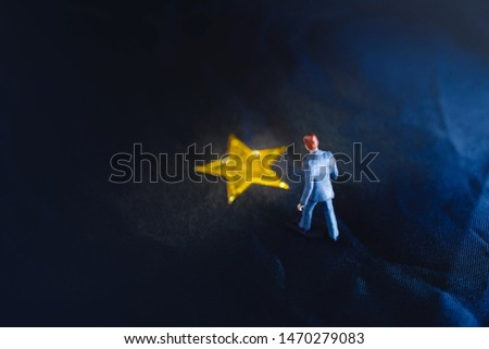 Success in Business or Talent Concept. Top View of a Miniature Businessman Standing on a Yellow Golden Star