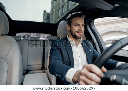 Success in motion. Handsome young man in full suit smiling while driving a car