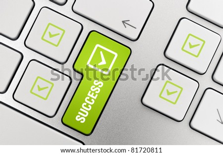Success Key concept. Button with success text and check mark symbols on modern aluminum computer keyboard.