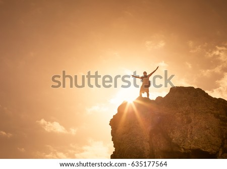 Success, life goals, fitness and achievement concept. Man standing on edge of mountain feeling victorious with arms up in the air.