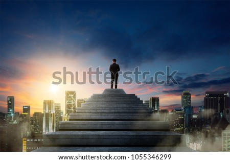 Success person climbed on top of the stairs looking at the cityscape. Success business concept.