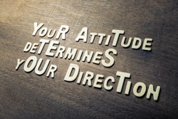 Success quote concept by wood alphabets arranged on wood wall, Your Attitude Determines Your Direction