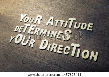 Success quote concept by wood alphabets arranged on wood wall, Your Attitude Determines Your Direction Stock foto ©