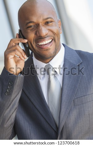 Successful African American businessman or man in a suit in a modern city talking on his cell phone