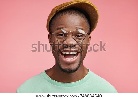 Successful African American male rejoices moving on career ladder or getting new profitable job, smiles gladfully, has attractive appearance. Dark skinned stylish guy pleased to recieve compliment