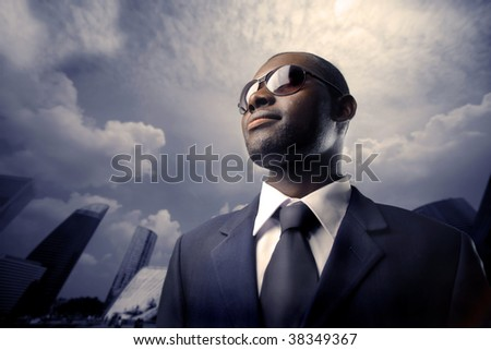 successful african manager surrounded by skyscrapers