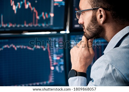 Photo of  Successful and concentrated trader in formalwear looking at monitor, analyzing global bitcoin price on network diagram, working in office