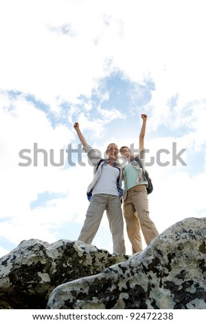 successful and happy hiking women on top of a rock