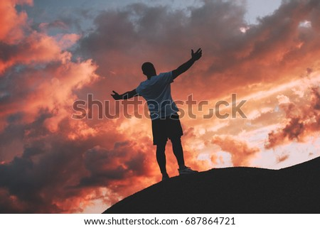 Successful and happy male athlete stands with his arms raised to the sunset #687864721