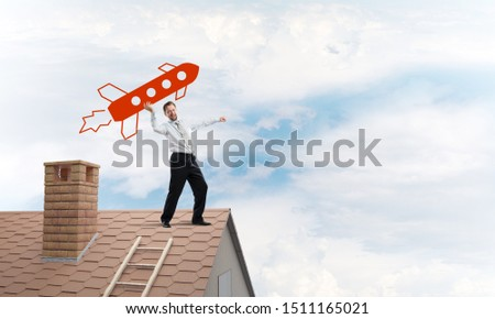 Successful and young businessman standing on the top of brick roof and throwing huge red rocket in the air with cloudy skyscape view on background. #1511165021