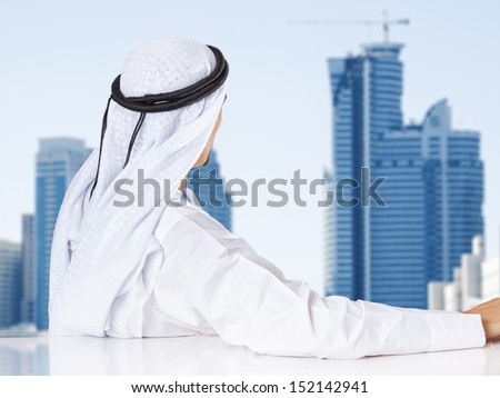 Successful Arab businessman looking out the window of his office.