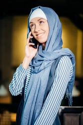 Successful Arab woman. Arab businesswoman wearing hijab talking on cell phone and looking at the camera