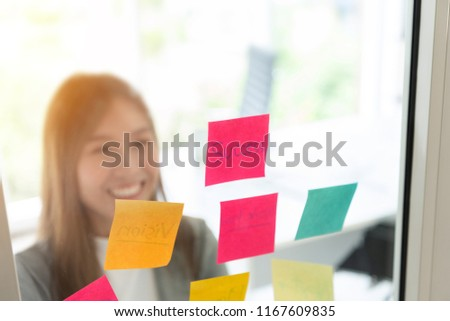 Successful Asian Business woman is looking to sticky note paper on clear glass wall. Smiling face. #1167609835