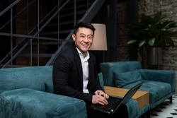 Successful Asian businessman, in a black business suit, works on a laptop, relaxes in a restaurant or hotel, and in a stylish office explains a new business strategy via video link