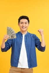 Successful Asian man. Happy young man holding money while standing and arms up, isolated on yellow background
