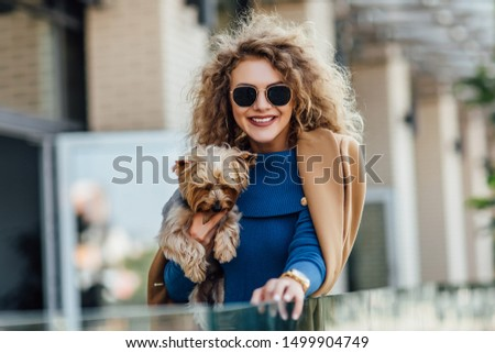Successful attractive woman wearing at nude coat looking at camera and holding Yorkshire terrier. Yorkshire terrier concept. #1499904749