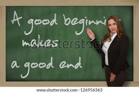 Successful, beautiful and confident woman showing A good beginning makes a good end on blackboard