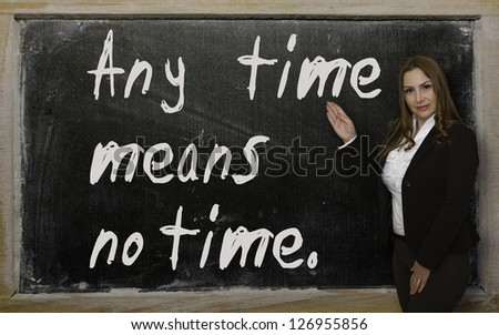 Successful, beautiful and confident woman showing Any time means no time on blackboard