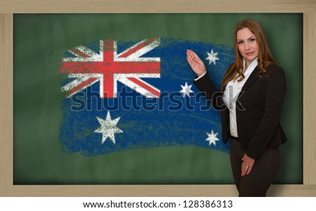 Successful, beautiful and confident woman showing flag of australia on blackboard for marketing research, presentation and tourist advertising