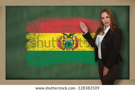 Successful, beautiful and confident woman showing flag of bolivia on blackboard for marketing research, presentation and tourist advertising