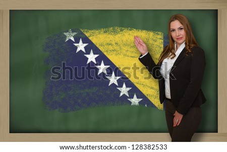 Successful, beautiful and confident woman showing flag of bosnia herzegovina on blackboard for marketing research, presentation and tourist advertising