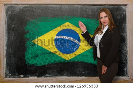 Successful, beautiful and confident woman showing flag of Brazil on blackboard for marketing research, presentation and tourist advertising