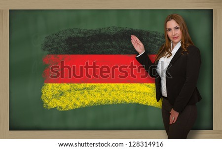 Successful, beautiful and confident woman showing flag of germany on blackboard for marketing research, presentation and tourist advertising