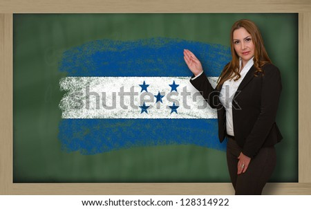 Successful, beautiful and confident woman showing flag of honduras on blackboard for marketing research, presentation and tourist advertising