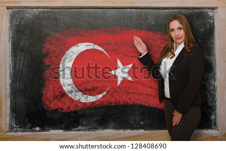 Successful, beautiful and confident woman showing flag of Turkey on blackboard for marketing research, presentation and tourist advertising