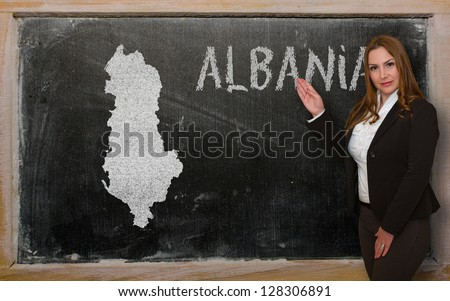 Successful, beautiful and confident young woman showing map of albania on blackboard for presentation, marketing research and tourist advertising