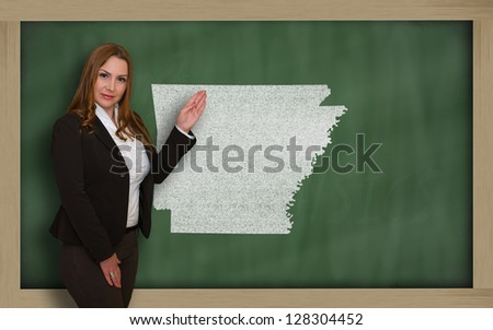 Successful, beautiful and confident young woman showing map of arkansas on blackboard for presentation, marketing research and tourist advertising