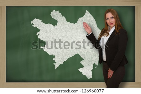 Successful, beautiful and confident young woman showing map of azerbaijan on blackboard for presentation, marketing research and tourist advertising