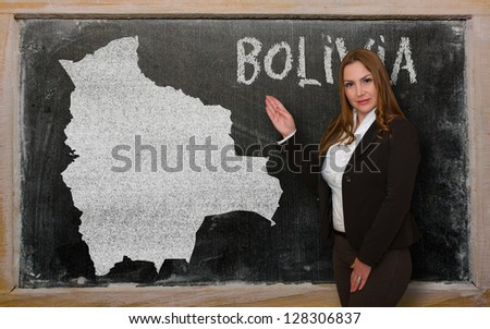 Successful, beautiful and confident young woman showing map of bolivia on blackboard for presentation, marketing research and tourist advertising