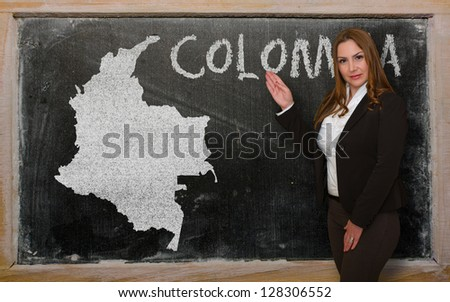 Successful, beautiful and confident young woman showing map of colombia on blackboard for presentation, marketing research and tourist advertising