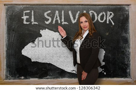 Successful, beautiful and confident young woman showing map of el salvador on blackboard for presentation, marketing research and tourist advertising
