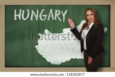 Successful, beautiful and confident young woman showing map of hungary on blackboard for presentation, marketing research and tourist advertising
