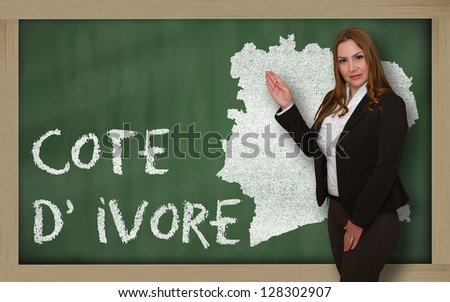 Successful, beautiful and confident young woman showing map of ivory coast on blackboard for presentation, marketing research and tourist advertising