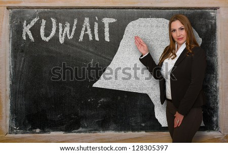 Successful, beautiful and confident young woman showing map of kuwait on blackboard for presentation, marketing research and tourist advertising