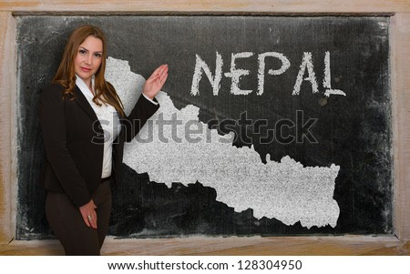 Successful, beautiful and confident young woman showing map of nepal on blackboard for presentation, marketing research and tourist advertising