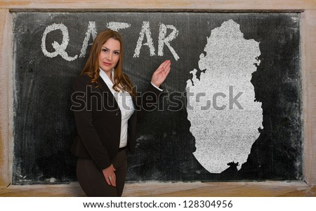 Successful, beautiful and confident young woman showing map of qatar on blackboard for presentation, marketing research and tourist advertising