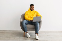 Successful Black Freelancer Guy Using Laptop Working Online Sitting In Armchair On Gray Wall Background Indoors. African American Millennial Man Browsing Internet On Computer Writing Article For Blog